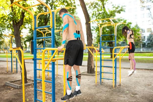 Vista lateral de um casal de atletas irreconhecíveis com fita elástica cinesiológica nos corpos, homem e mulher morena praticando mergulhos em barras paralelas