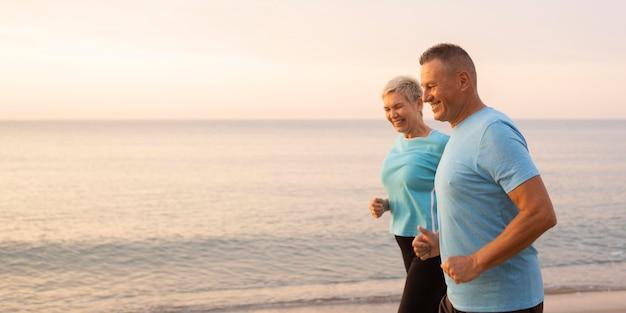 Vista lateral de um casal de idosos correndo juntos na praia