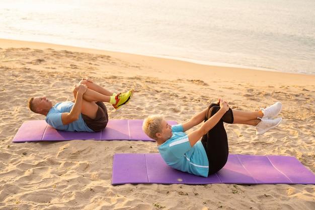 Vista lateral de um casal de idosos fazendo exercícios juntos na praia