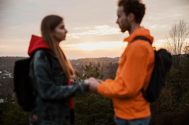 Vista lateral de um casal de mãos dadas ao pôr do sol em uma viagem.