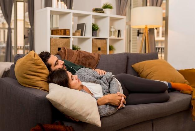 Vista lateral de um casal deitado no sofá