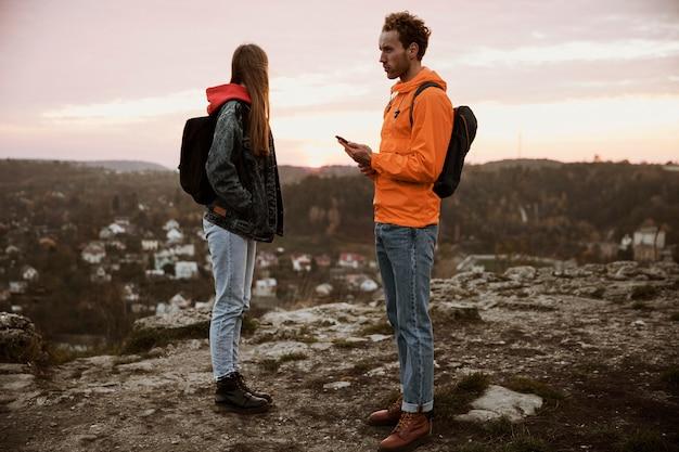 Vista lateral de um casal em uma viagem junto com uma bússola