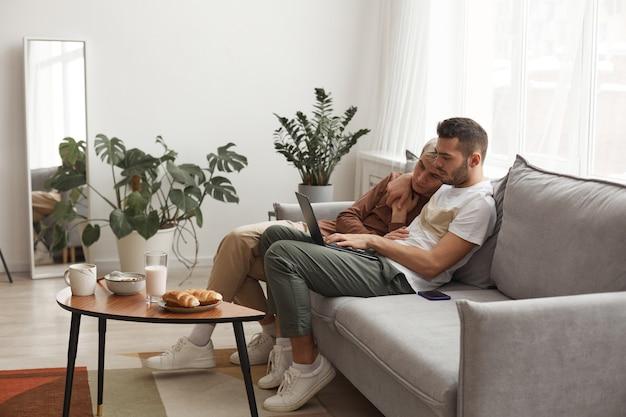 Vista lateral de um casal gay contemporâneo na vida cotidiana, dois jovens usando laptop juntos enquanto relaxam no sofá em casa, copie o espaço