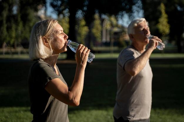 Vista lateral de um casal maduro bebendo água do lado de fora