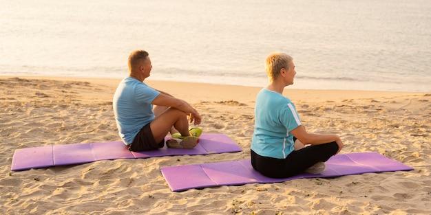 Vista lateral de um casal mais velho fazendo exercícios juntos na praia