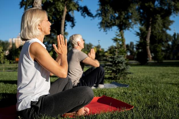 Vista lateral de um casal mais velho praticando ioga ao ar livre com espaço de cópia