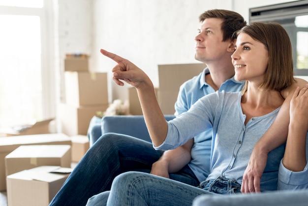 Vista lateral de um casal no sofá apontando para algo enquanto se move
