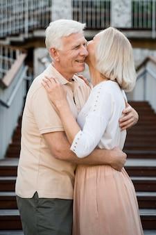 Vista lateral de um casal romântico sênior abraçado ao ar livre