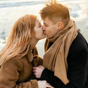 Vista lateral de um casal se beijando e se divertindo na praia no inverno