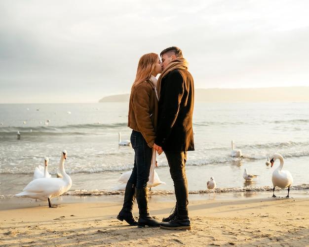 Vista lateral de um casal se beijando na praia no inverno