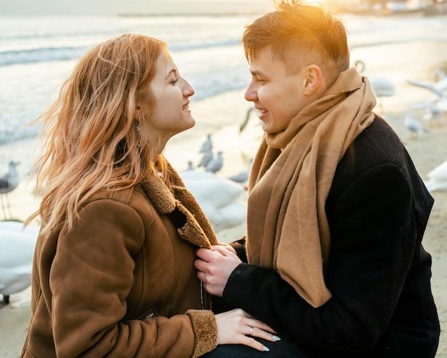 Vista lateral de um casal se divertindo na praia no inverno