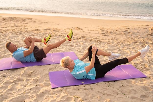 Vista lateral de um casal sênior fazendo exercícios juntos na praia