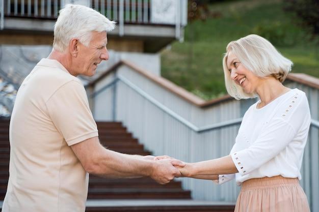 Vista lateral de um casal sênior romântico e amoroso de mãos dadas ao ar livre
