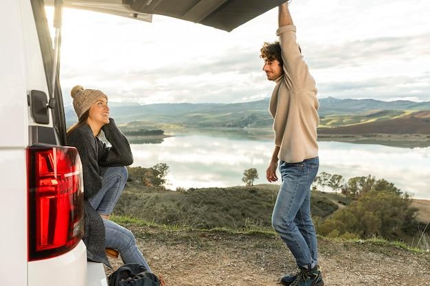 Vista lateral de um casal sentado no porta-malas do carro durante uma viagem