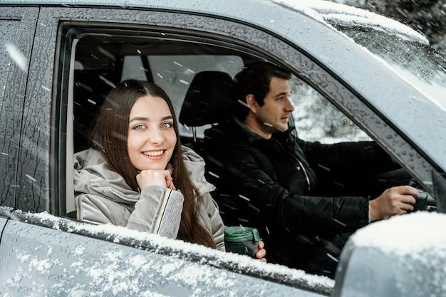 Vista lateral de um casal sorridente no carro durante uma viagem