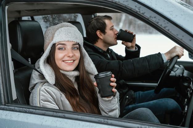 Vista lateral de um casal sorridente no carro tomando uma bebida quente durante uma viagem