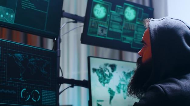 Vista lateral de um ciberterrorista barbudo vestindo um moletom. criminoso cibernético perigoso.