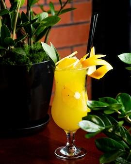 Vista lateral de um cocktail cítrico decorado com casca de laranja e rodelas de limão em vidro na mesa