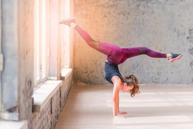 Vista lateral, de, um, condicão física, mulher jovem, fazendo, handstand, com, divisões