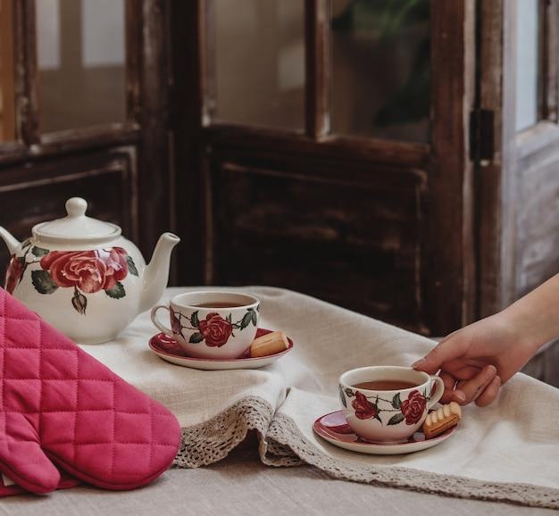 Vista lateral de um conjunto de chá de padrão floral rosa com um bule de chá e uma xícara de chá com biscoitos na toalha da mesa
