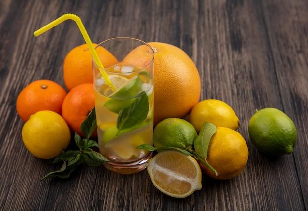 Vista lateral de um copo d'água com rodelas de limão e hortelã com canudo amarelo e toranja com laranjas em fundo de madeira