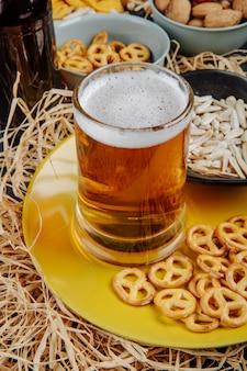 Vista lateral de um copo de cerveja com mini pretzels e sementes de girassol no prato amarelo em palha