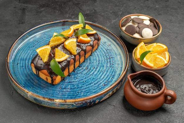 Vista lateral de um delicioso bolo decorado com laranja e chocolate com outros biscoitos na mesa escura