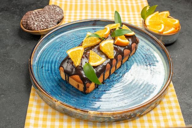 Vista lateral de um delicioso bolo decorado em uma toalha amarela listrada e biscoitos na mesa preta