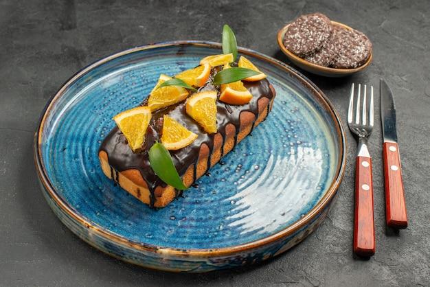 Vista lateral de um delicioso bolo e biscoitos com garfo e faca na mesa preta