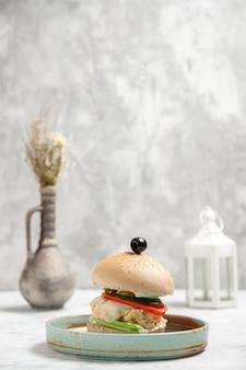 Vista lateral de um delicioso sanduíche caseiro com azeitona preta em um prato e acessórios em uma superfície branca manchada