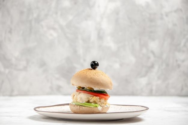 Vista lateral de um delicioso sanduíche caseiro em um prato na superfície branca manchada