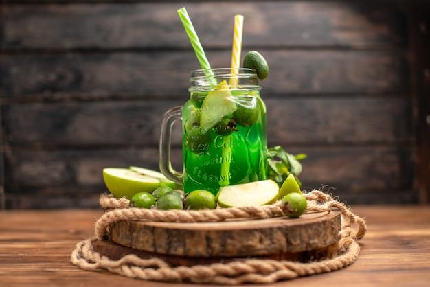 Vista lateral de um delicioso suco de fruta fresco servido com maçã e feijoas em uma tábua de madeira