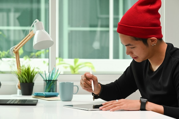 Vista lateral de um designer gráfico com chapéu de lã vermelha, trabalhando em tablet digital em sua estação de trabalho.