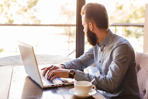 Vista lateral, de, um, digitando homem, ligado, laptop, keypad, com, xícara café, escrivaninha