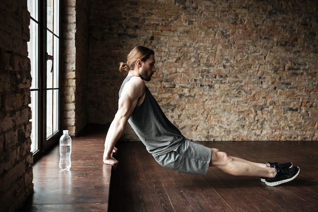 Vista lateral de um esportista fazendo exercícios no peitoril da janela