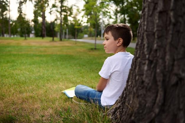 Vista lateral de um estudante distraído descansando depois da escola, sentado na grama verde do parque da cidade, encostado em uma árvore, fazendo sua lição de casa e se distraindo com seu ambiente. de volta à escola