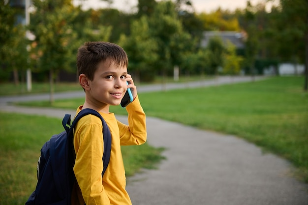 Vista lateral de um estudante vestindo um moletom amarelo com mochila andando no caminho em um parque público, indo para casa depois da escola, falando no celular, sorrindo com um sorriso cheio de dentes para a câmera