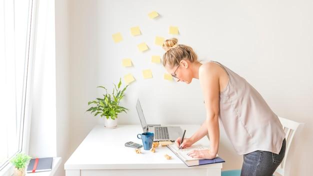 Vista lateral, de, um, executiva, escrita, cronograma, em, diário, em, local trabalho