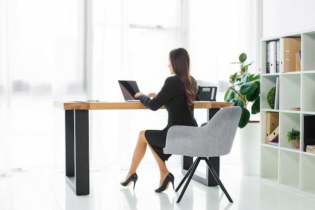 Vista lateral, de, um, executiva, usando computador portátil, em, escritório