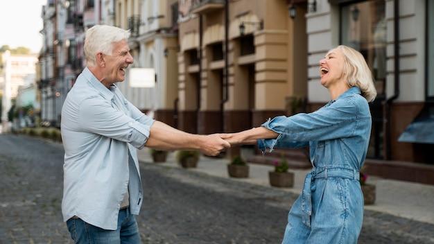 Vista lateral de um feliz casal de idosos passando um tempo na cidade