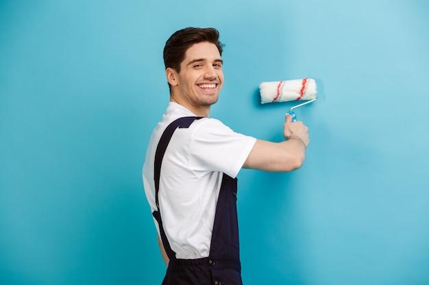 Vista lateral de um feliz construtor masculino pintando a parede com rolo de tinta enquanto sobre a parede azul