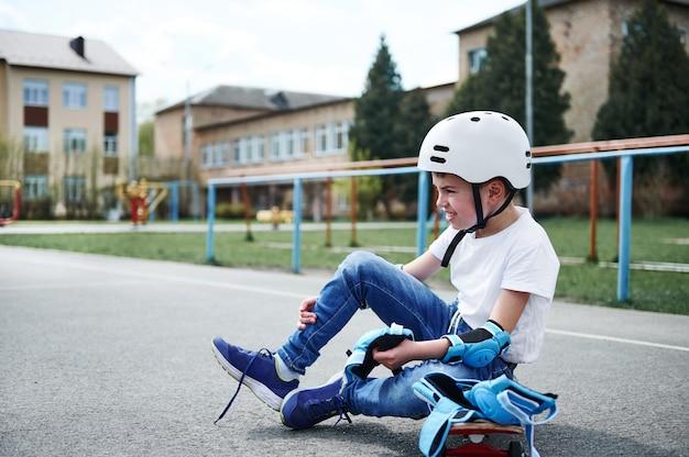 Vista lateral de um garoto esportivo usando capacete de segurança, sentado em um skate de madeira e colocando joelheiras protetoras