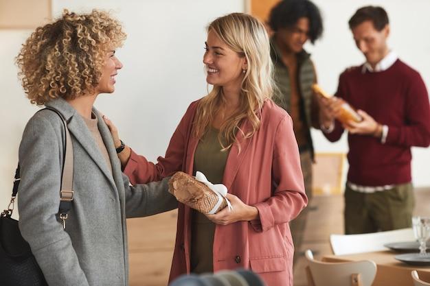 Vista lateral de um grupo de adultos elegantes se cumprimentando e trocando presentes enquanto dão as boas-vindas aos convidados em um jantar dentro de casa