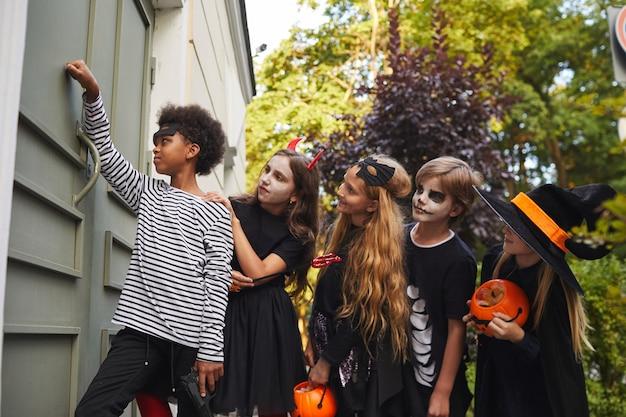 Vista lateral de um grupo multiétnico de crianças vestindo fantasias de halloween, tocando a campainha enquanto fazem doces ou travessuras juntos, copie o espaço