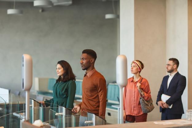 Vista lateral de um grupo multiétnico de executivos em pé na fila ao passar por um portão automatizado para entrar no prédio comercial, foco em uma jovem mulher do oriente médio passando o cartão de identificação, copie o espaço
