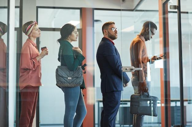 Vista lateral de um grupo multiétnico de executivos em pé na fila do escritório atrás de uma parede de vidro, copie o espaço