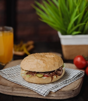 Vista lateral de um hambúrguer com carne e suco em um copo na mesa