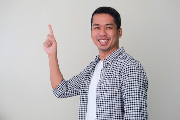 Vista lateral de um homem adulto asiático apontando para cima com uma expressão de rosto feliz