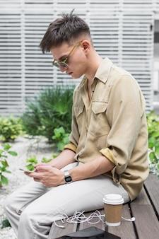 Vista lateral de um homem ao ar livre olhando para o smartphone e tomando café