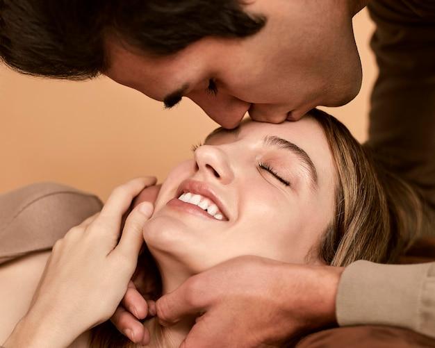 Vista lateral de um homem beijando uma mulher sorridente na testa